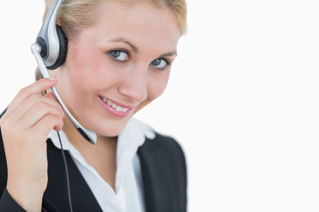 Close-up portrait of young business woman wearing headset over white background photo