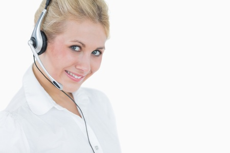 Close-up portrait of young female executive wearing headset over white background photo