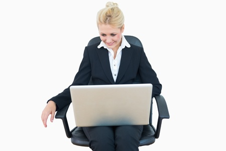 Happy young business woman using laptop on chair over white background photo