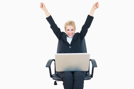 Successful young business woman raising hands with laptop over white background photo