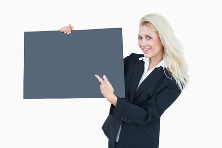 Portrait of young business woman pointing at empty banner over white background photo