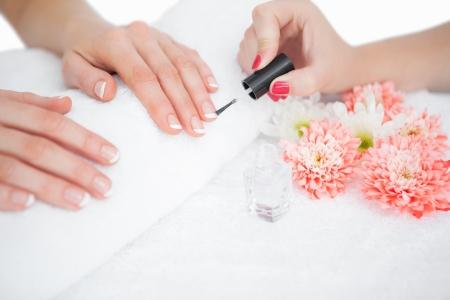 Close-up of woman applying nail varnish to finger nails at nail salon photo