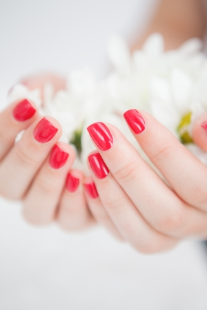 Close-up of manicured hands holding flowers at spa center