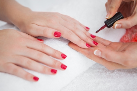 Close-up of woman applying nail varnish to finger nails at nail salon Stock Photo - 18124324