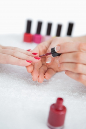 Close-up of woman applying nail varnish to finger nails at nail salon photo