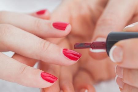nails: Details shot of hands applying red nail varnish to finger nails at nail salon