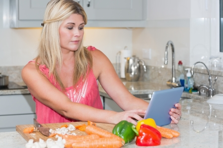 Woman cooking whilst looking at digital tablet in the kitchen at home photo