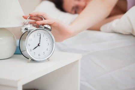extending: Close-up of sleepy woman in bed extending hand to alarm clock