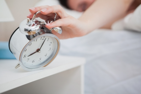 despertador: Primer plano de la mujer en la cama extendiendo la mano con el reloj de alarma Foto de archivo