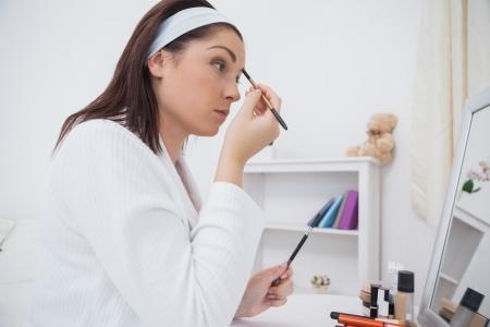 Vista laterale della giovane donna messa sul make-up