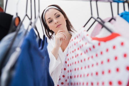 Young woman looking at clothing in closet photo