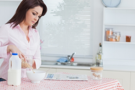 Young woman pouring cereal in bowl at kitchen worktop photo