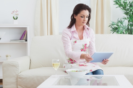 Casual young woman with wine and bowl looking at digital tablet on sofa photo