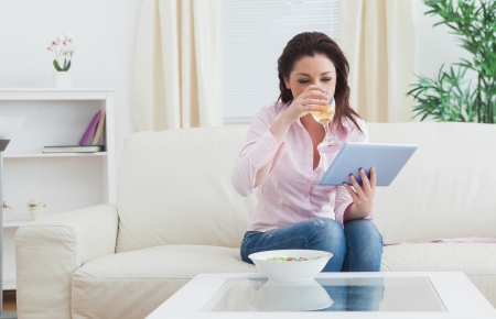 Casual young woman drinking wine while looking at digital tablet on sofa photo