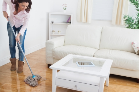 sitting floor: Young woman  mopping living room floor Stock Photo