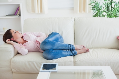 Casual young woman resting on  couch with digital tablet on table photo