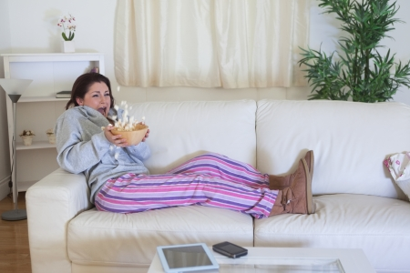 Scared young woman throwing popcorn while watching film on couch at home photo