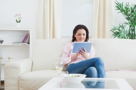 Casual happy young woman with wine and bowl using digital tablet on sofa photo