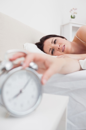 extending: Close-up of woman in bed extending hand to alarm clock