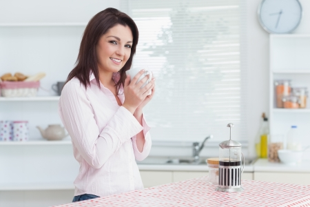 Portrait of smiling young woman with cup of coffee in the kitchen photo