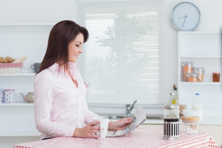 Side view of young woman reading newspaper while having coffee in the kitchen photo