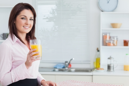 Portrait of smiling young woman with orange juice in the kitchen photo
