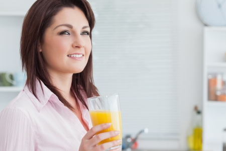 verre jus orange: Gros plan de femme souriante jeune jus d'orange dans la cuisine