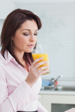 Young woman drinking orange juice in the kitchen photo