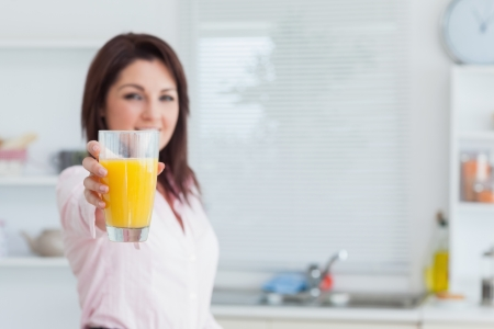 Portrait of smiling woman offering you orange juice in the kitchen photo