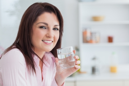 Close-up portrait of young woman with glass of water in the kitchen photo