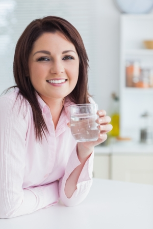Portrait of young woman with glass of water in the kitchen photo