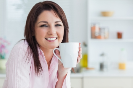 Portrait of young woman with coffee cup in the kitchen photo