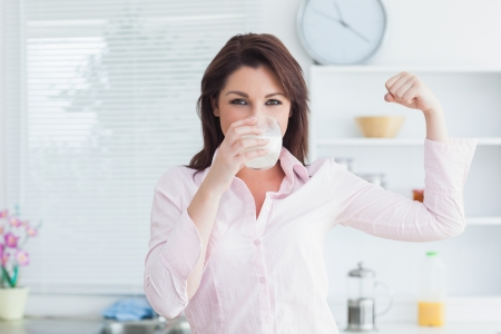 woman drinking milk: Portrait of young woman drinking milk and flexing muscles in the kitchen