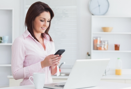 Young woman with coffee cup and laptop using cellphone in the kitchen photo