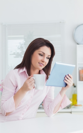Young woman with coffee cup looking at digital tablet in the kitchen photo