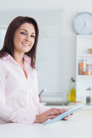 Portrait of young woman using digital tablet in the kitchen photo