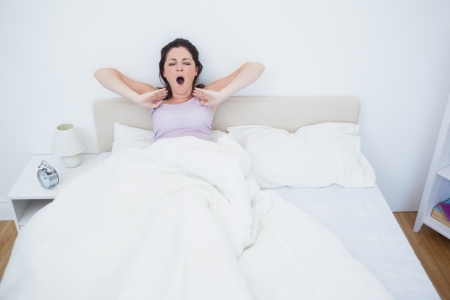 Sleepy young woman sitting and yawning in bed photo