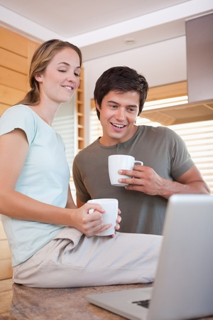 Young couple using laptop while drinking coffee in the kitchen photo