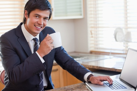 Portrait of smiling business man using laptop while drinking coffee in the kitchen photo