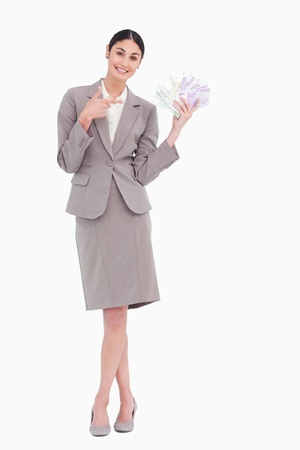 Portrait of happy business woman pointing at banknotes over white background Stock Photo - 18100821
