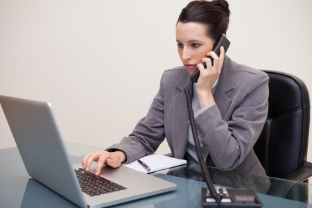Young business woman using laptop while on call at office photo