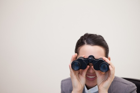 Business woman looking through binoculars over white background photo