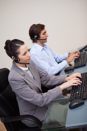 Side view of call center employees at work photo