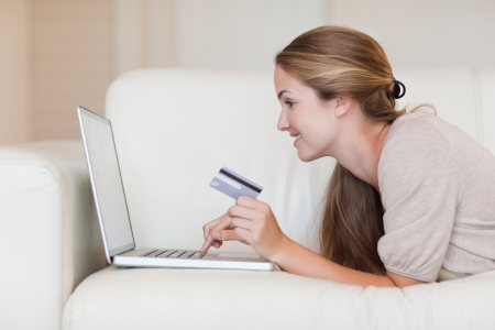 Side view of casual woman doing online shopping through laptop and credit card photo