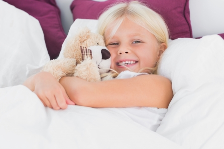 cuddly toy: Little girl embracing her cuddly toy on the bed  Stock Photo