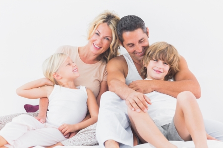 Family posing on a bed in the bedroom photo