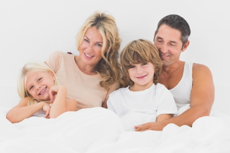 blonde hispanic: Family lying on a white bed in the bedroom