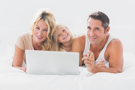 Family lying on a bed with laptop in the bedroom photo