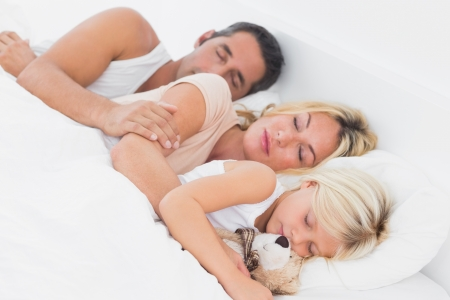 Family sleeping together on a same bed photo