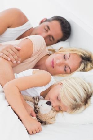 mujer en la cama: Familia en calma durmiendo juntos en una misma cama Foto de archivo